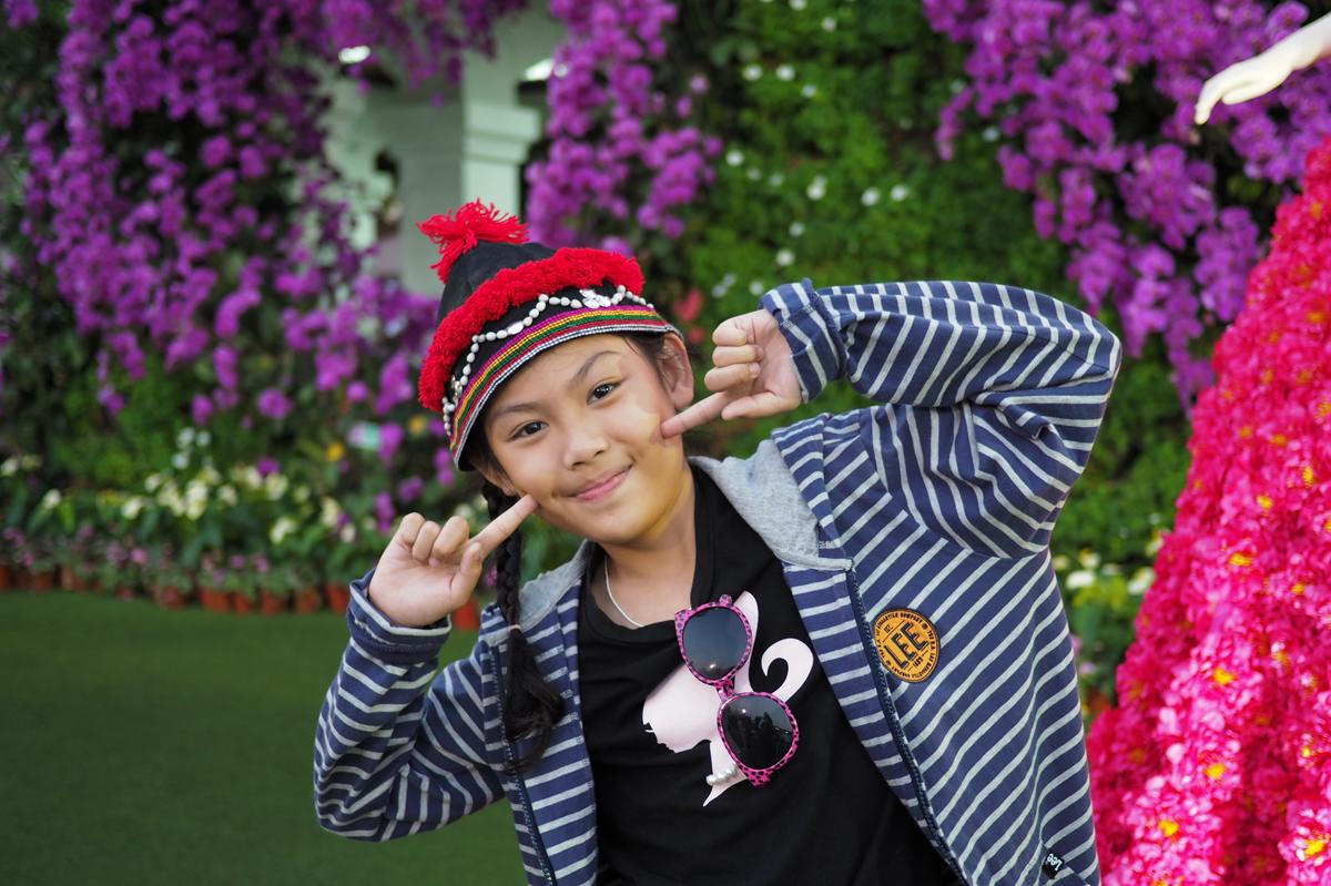 チェンラーイ花祭り会場でおどけたポーズをとる少女.jpg
